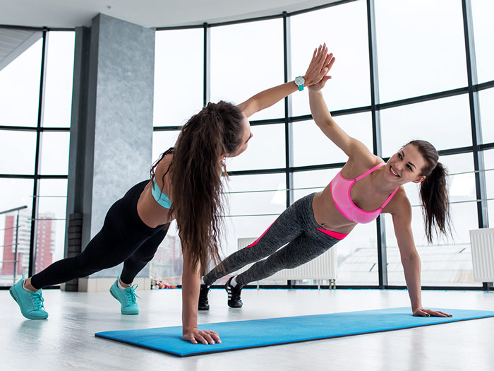 two women exercising together showing they are perfect gym partners