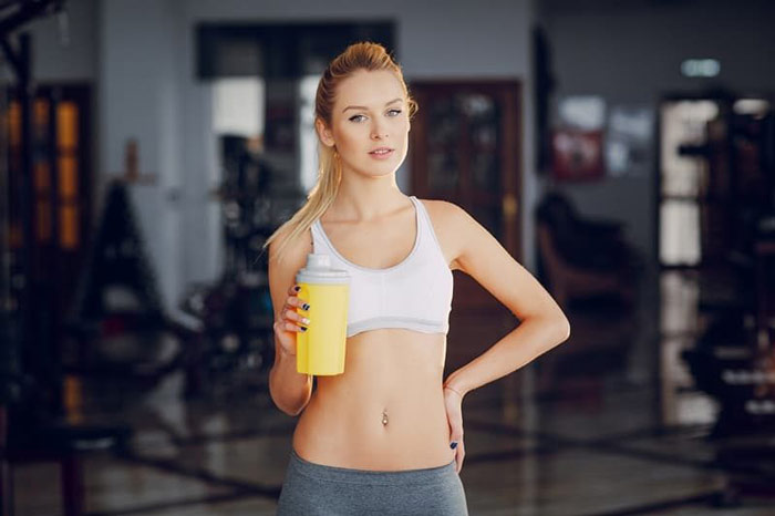 blonde female fitness athlete drinking creatine