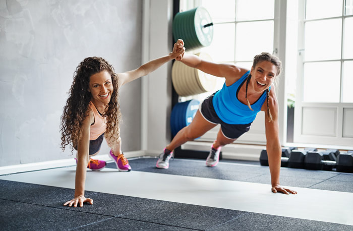 two women with positive mental attitude showing that they are perfect workout partners