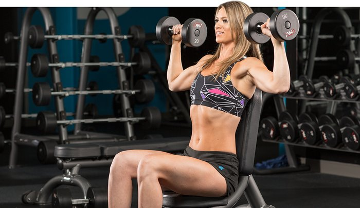 woman performing a seated dumbbell press