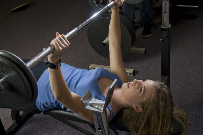 Woman at the top of a bench press movement