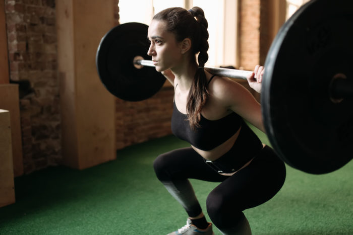 Woman doing a weighted squat in the gym as part of the essential lifts for women