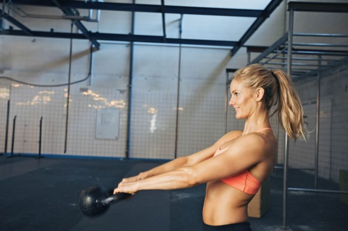 Woman swinging kettlebell for a workout