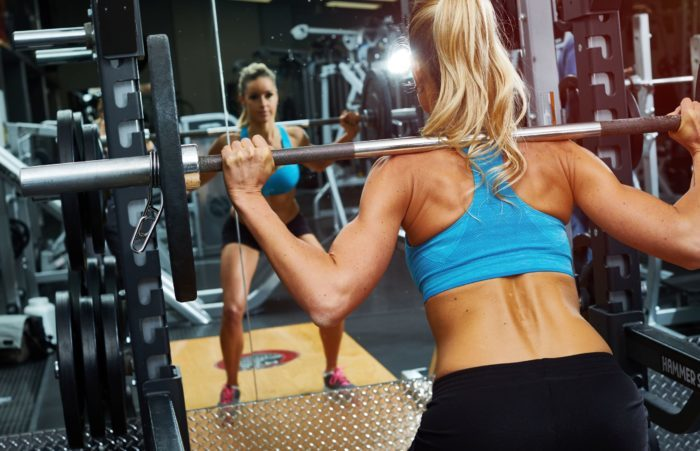 strong woman exercising her weighted squat