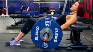female athlete performing barbell hip thrust