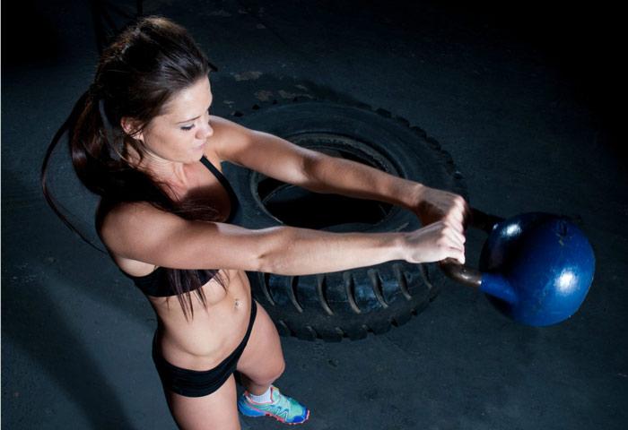 female athlete performing kettlebell swings