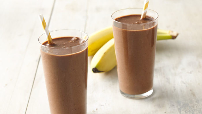 two high-protein chocolate smoothies with a banana in the background