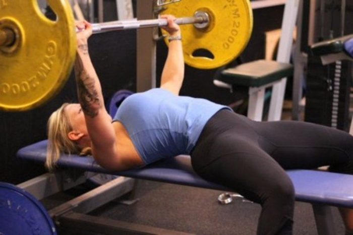 Woman at the top of a bench press