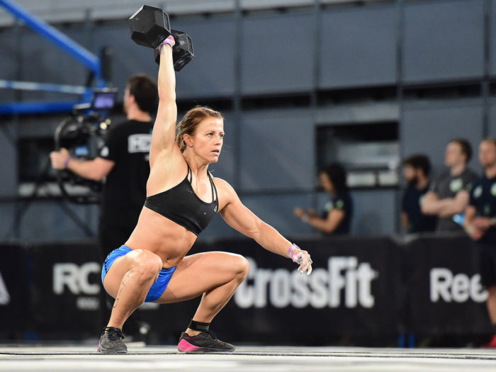 Woman competing in a crossfit competition at the bottom of a dumbbell snatch