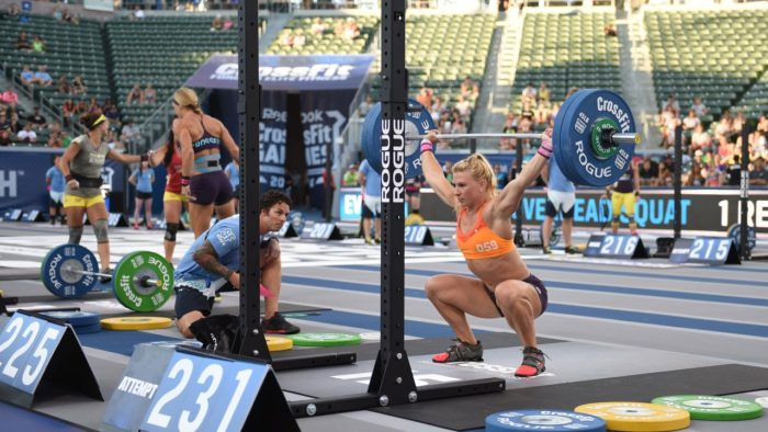 Woman competing in a crossfit competition, at the bottom of an overhead squat