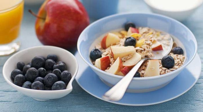 a bowl of oats with apple and blueberries