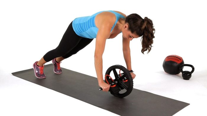 woman doing a ab wheel roll out to strengthen her core