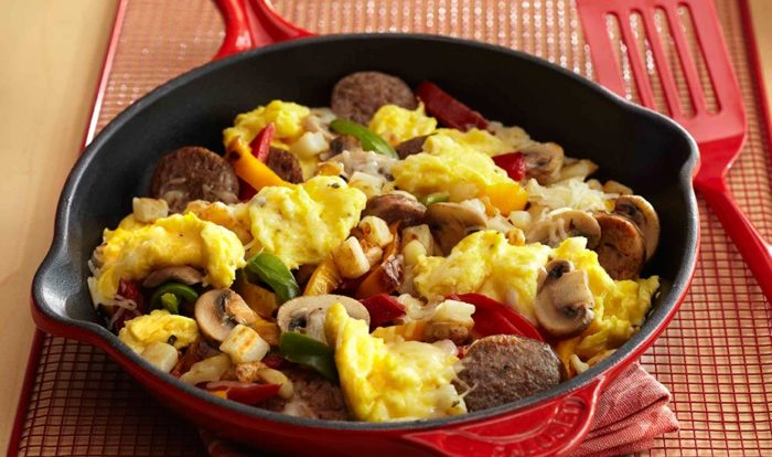 a skillet of chicken sausages, eggs and veg