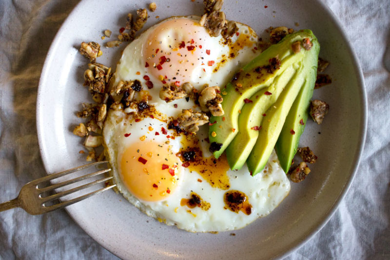eggs with walnuts, chilli flakes and avocado on a plate for breakfast