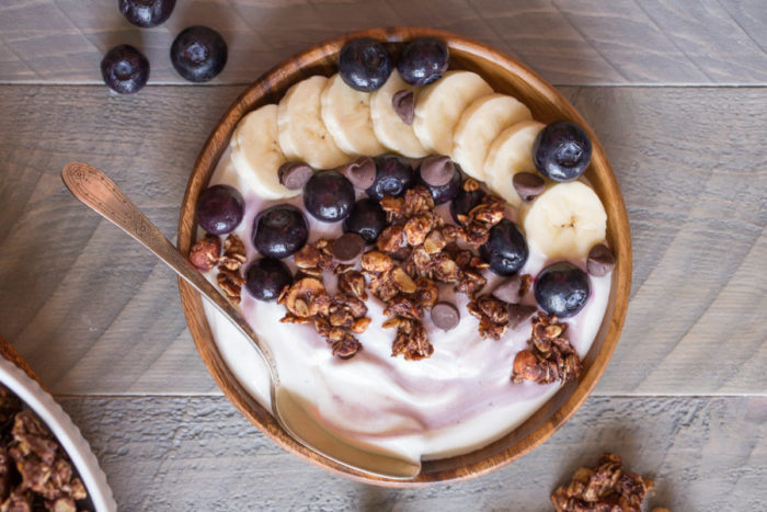 bowl of yogurt with bananas, granola and blueberries on top