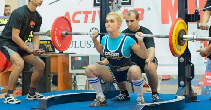 Woman competing in powerlifting at the bottom of a squat