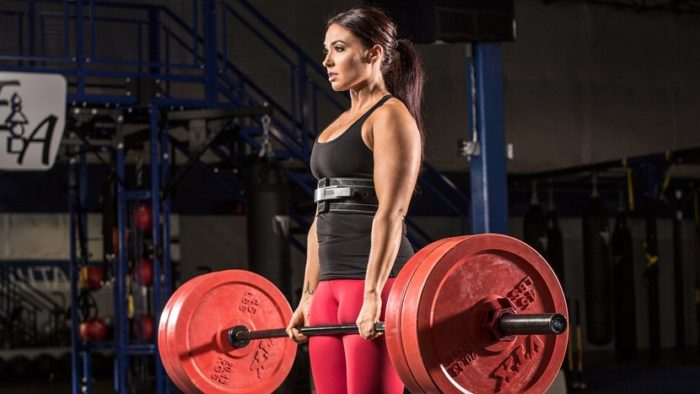 Woman a the top of a deadlift in powerlifting vs bodybuilding