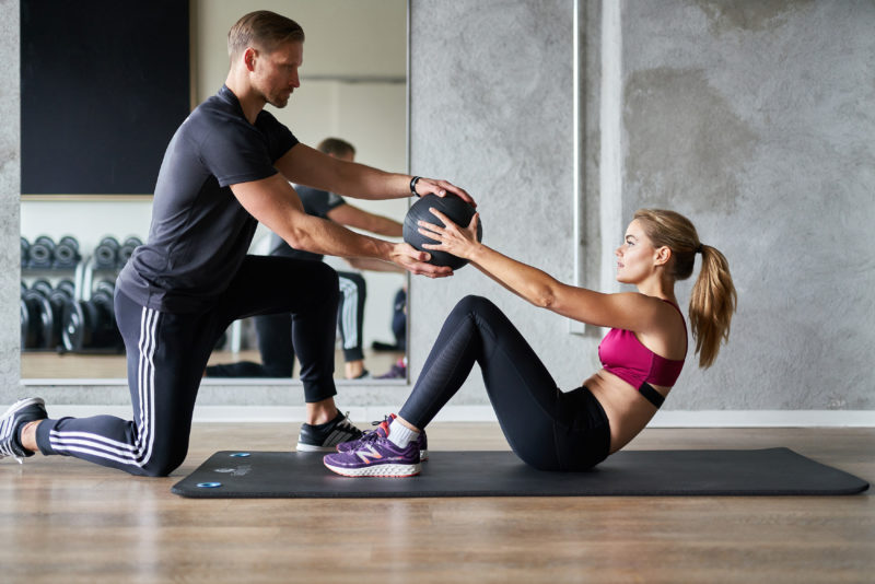 Male PT working out with a female client
