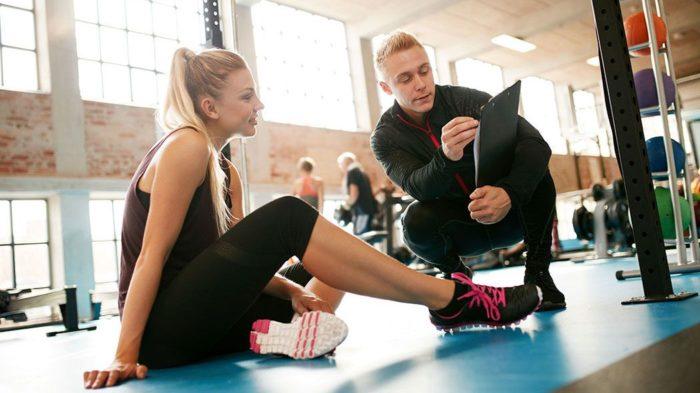 Male PT showing a female client a workout plan