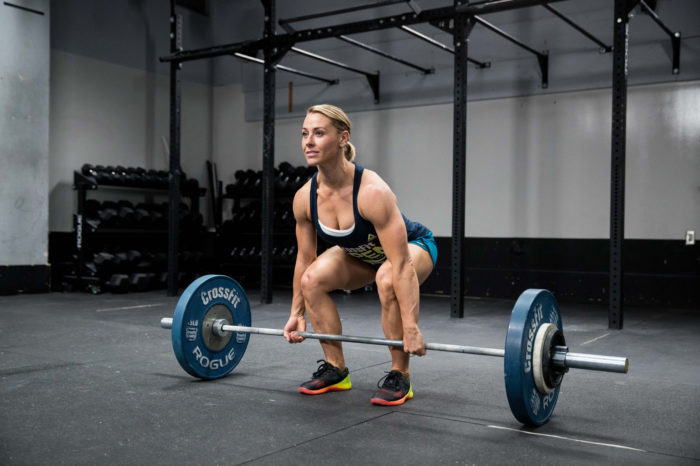 Woman about to perform a deadlift with a weighted barbell