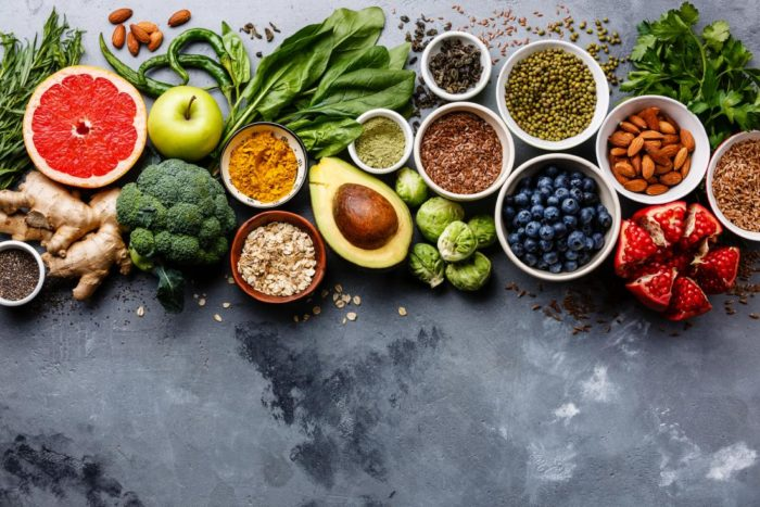 Selection of healthy, clean foods including brocolli, blueberries, almonds and avocado
