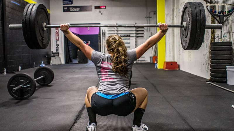 CrossFit female athlete performing overhead squat