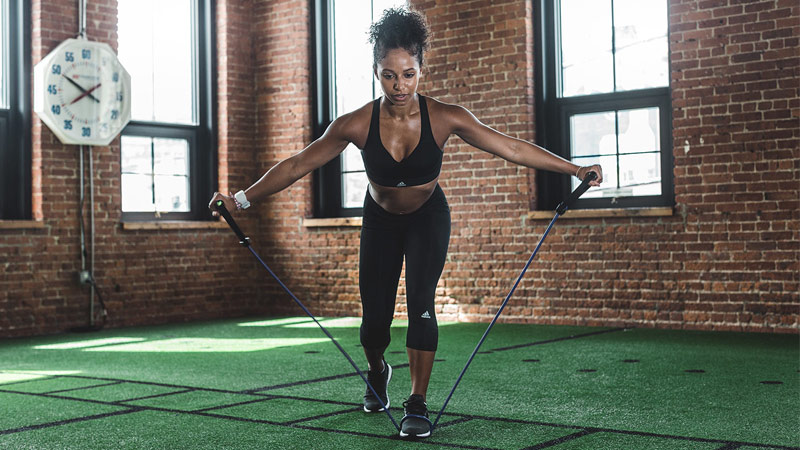 Fit, strong and athletic woman performing workout with resistance band in gym studio
