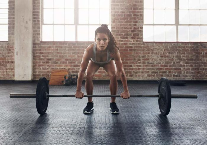 Woman at the bottom of a deadlift in a beginners fat loss workout
