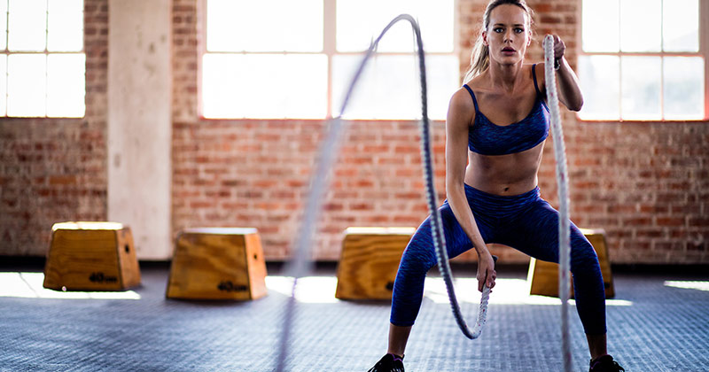 woman exercising with battle ropes as part of Tabata circuit