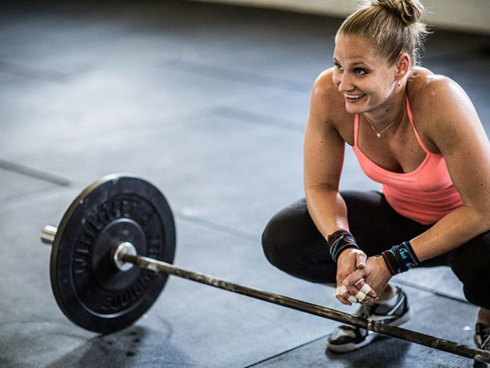 Woman squatting next to a barbell