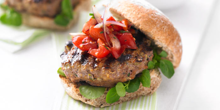 A healthy burger with brown bread and fresh peppers on top