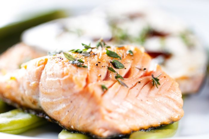 A close up of a cooked salmon fillet with seasoning on top
