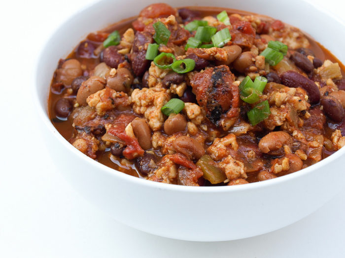 A bowl of tempeh chili with beans and chives on top