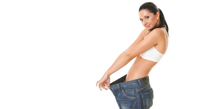 Slim woman pulling out trousers that are too large for her at the waist