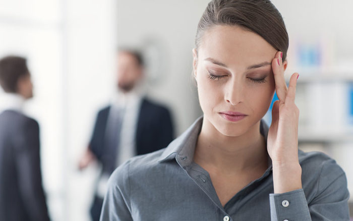 Woman holding her head to indicate she has a headache