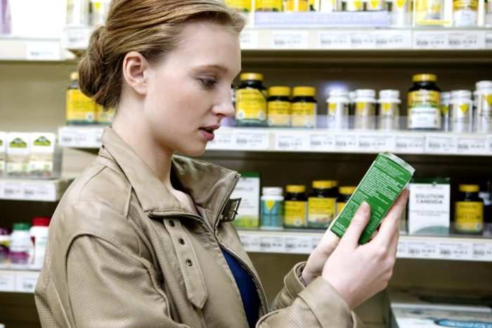 Woman reading the label of a fat burner supplement