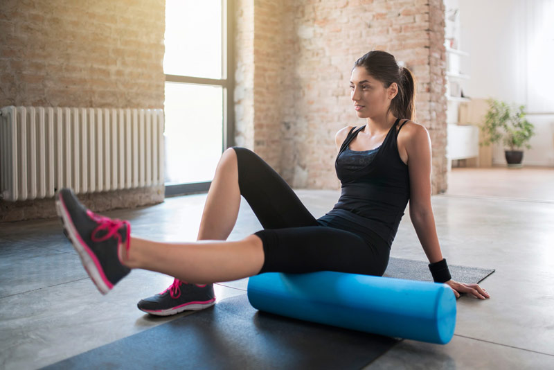 young woman foam rolling hamstring muscle