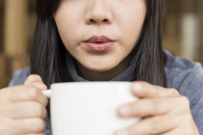 woman drinking out of a coffee cup