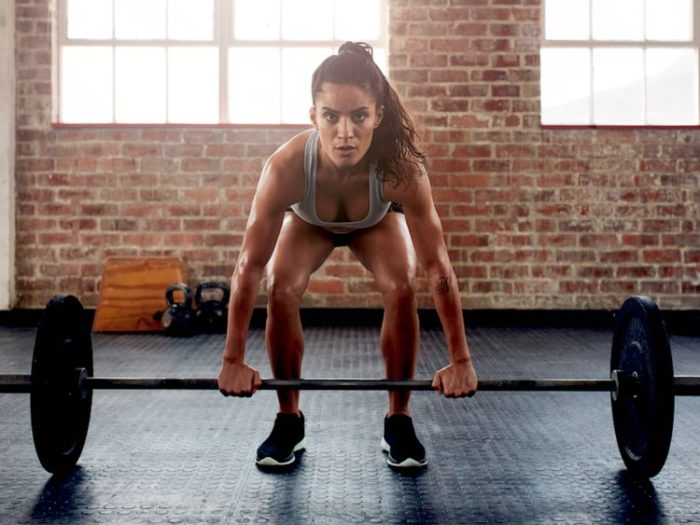 Woman about to do a deadlift with a weighted bar