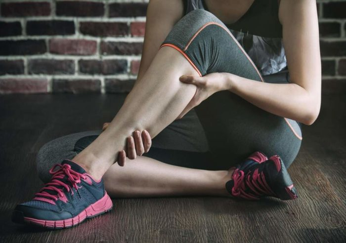 Woman in the gym clutching her injured calf