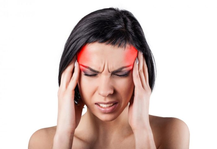 Woman holding her head because she has a headache