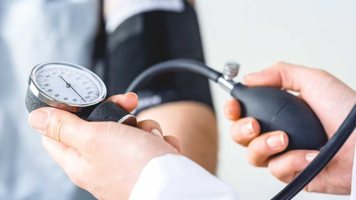 A doctor holding a blood pressure monitor and measuring someones blood pressure