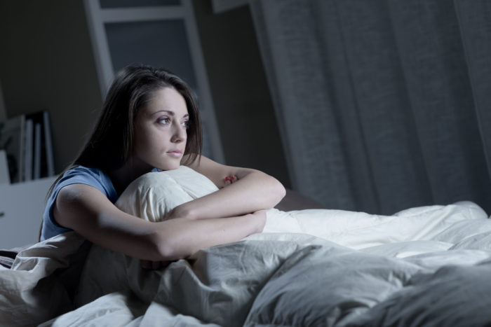 Woman struggling to sleep as part of a pre-workout side effect