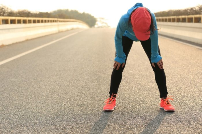A woman bent over with her hands on her knees after a long run.
