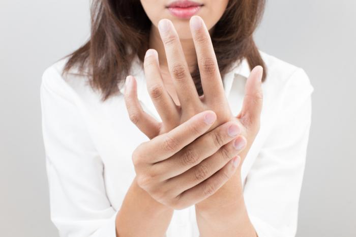 Woman holding her hand to represent hand tingles