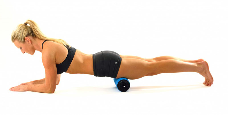 fit and healthy female foam rolling quadriceps muscle