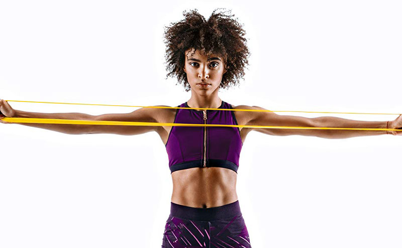 young, fit and healthy woman performing resistance band pull apart