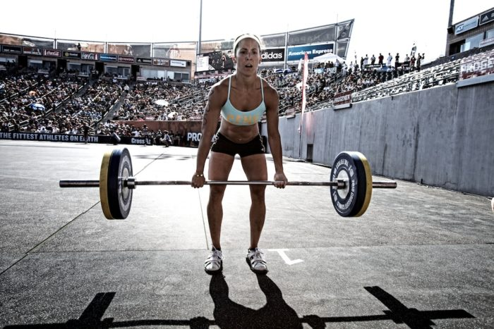 Woman in a competition halfway through a deadlift