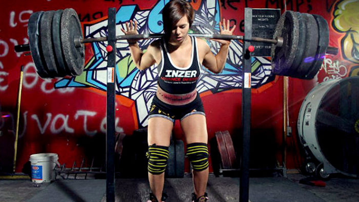 Woman about to perform a heavy squat with a heavily weighted bar across her back