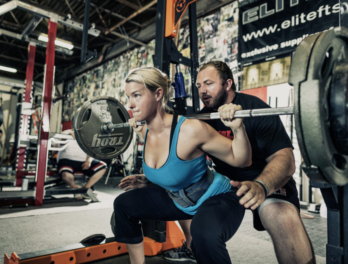 Woman at the bottom of a squat with a male spotter behind her